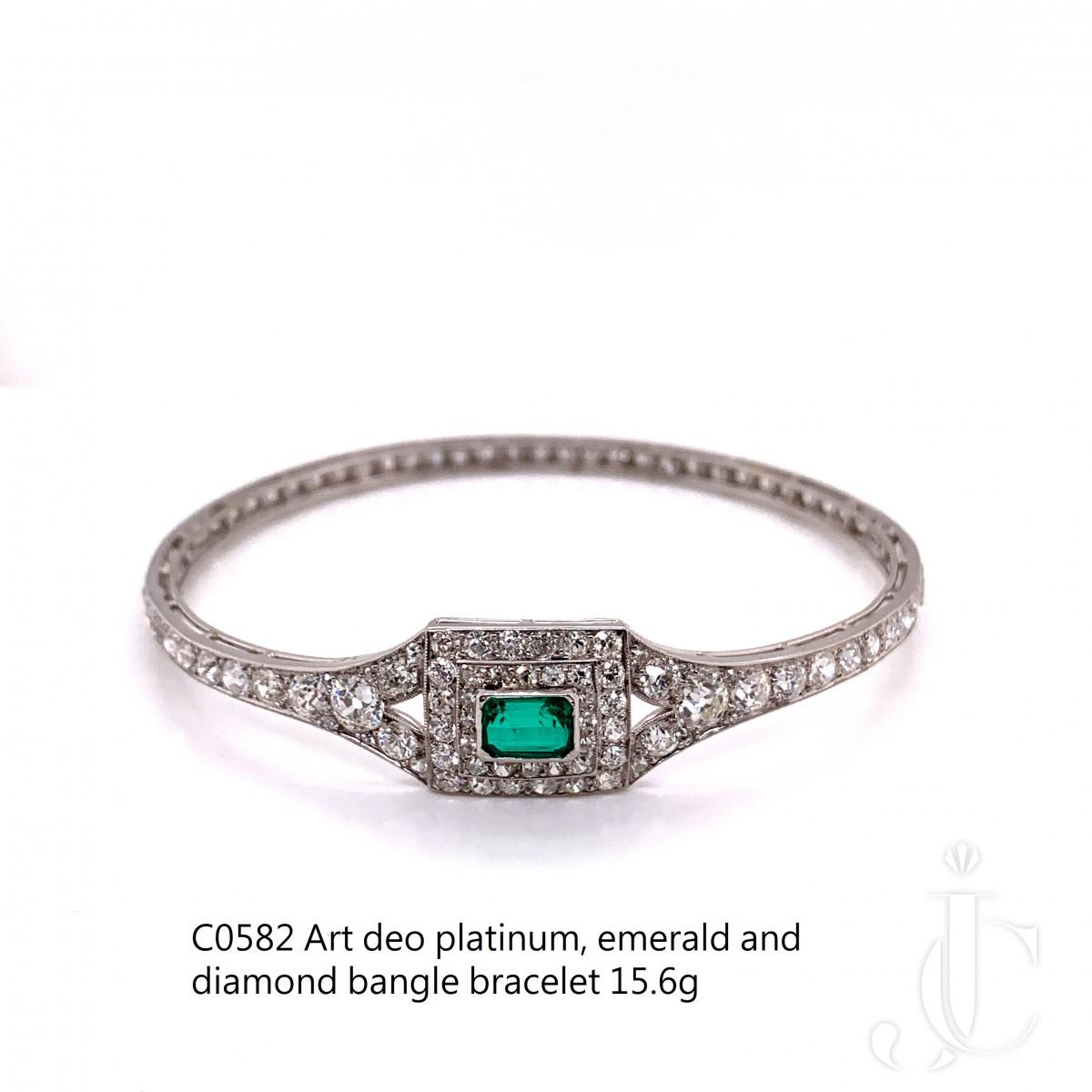 A platinum, emerald and diamond bangle bracelet by Cartier
