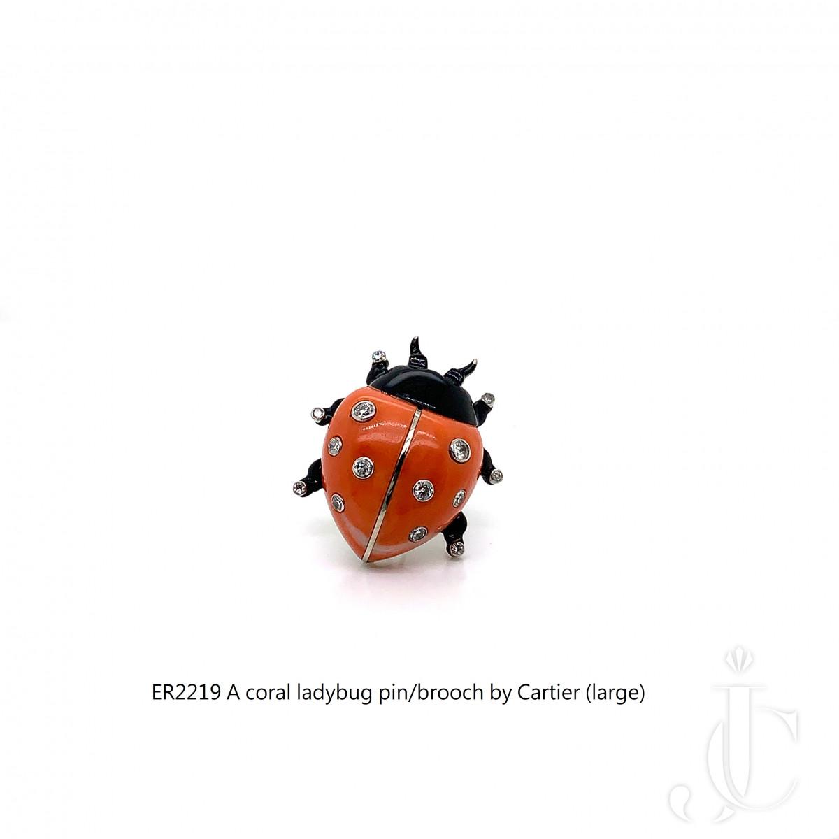 A platinum coral ladybug pinbrooch by Cartier